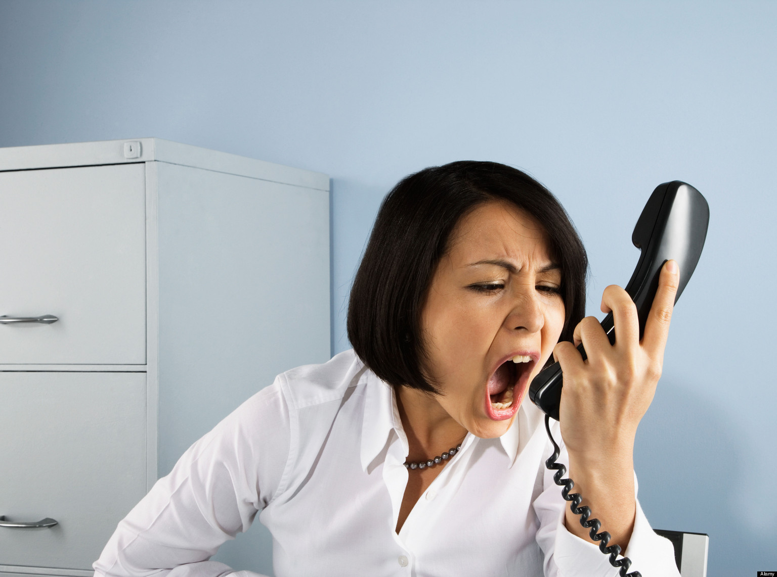 B2T86N Businesswoman shouting at telephone. Image shot 2008. Exact date unknown.